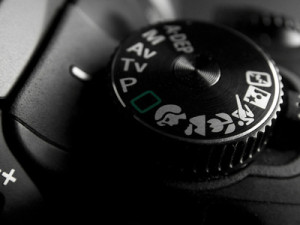 The aperture, shutter, and ISO buttons on a DSLR camera